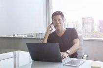 Красивый азиатский бизнесмен, работающий с ноутбуком в офисе — стоковое фото