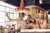 Компания молодых азиатских друзей вместе празднуют Рождество и делают селфи — стоковое фото