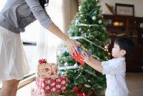 Азіатський сімейні святкування свята Різдва, матері, даючи подарунок Сину — стокове фото