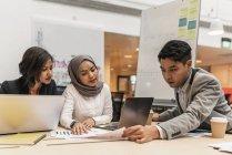 Giovani imprenditori multiculturale lavorando con dispositivi digitali e documenti in ufficio moderno — Foto stock