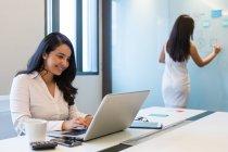 Duas jovens que trabalham juntas numa sala de conferências — Fotografia de Stock