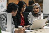 Молодой многокультурного деловых людей, работающих с ноутбуком в современном офисе — стоковое фото