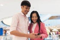 Attrayant jeune asiatique couple en utilisant smartphone ensemble — Photo de stock