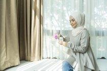 Asiatique mère musulmane, préparation de lait pour bébé. — Photo de stock