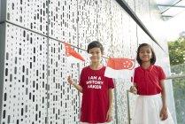 Frères et sœurs qui célèbrent la fête nationale de Singapour — Photo de stock