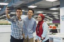 Junge asiatische Geschäftsleute machen Selfie im modernen Büro — Stockfoto