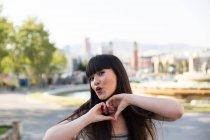 Giovane donna eurasiatica mostrando il cuore con le dita alla macchina fotografica — Foto stock
