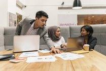 Jóvenes empresarios multiculturales que trabajan en oficinas modernas - foto de stock