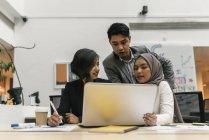 Gente de negocios multicultural jóvenes trabajando con el portátil en la oficina moderna - foto de stock