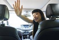 Fröhliche Autofahrerin gibt ihrem Beifahrer eine Hallo-Fünf — Stockfoto