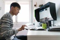 Jeune homme asiatique travaillant à la maison, vue latérale — Photo de stock