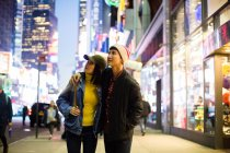 Young asian couple exploring time square in night time — Stock Photo