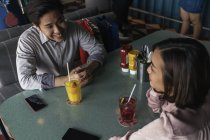 Young asian couple spending time together in bar — Stock Photo