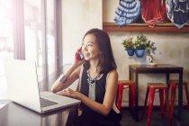Giovane bella donna asiatica utilizzando smartphone e laptop in caffè — Foto stock