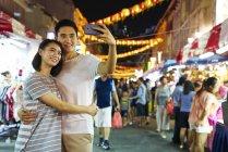 Молодая азиатская пара проводит время вместе на традиционном базаре в китайском Новом году и делает селфи — стоковое фото