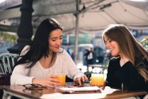 Beautiful friends with a smart phone in the streets of Spain sitting in a cafeteria — Stock Photo
