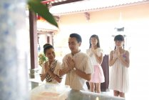 Young happy asian family praying in shrine — Stock Photo