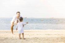 Família caucasiana feliz na praia, menina apontando em algo — Fotografia de Stock