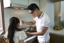 Father feeding little daughter at kitchen — Stock Photo