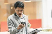 Jovem asiático homem de negócios usando smartphone no escritório moderno — Fotografia de Stock