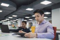 Jóvenes asiático negocios hombres trabajando en moderno oficina - foto de stock