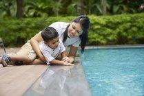 Мати і син склеювання біля басейну — стокове фото