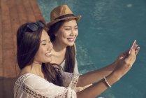 Привлекательные молодые азиатские женщины, делающие селфи у бассейна — стоковое фото