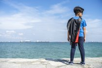 Vista posteriore del bambino supereroe in piedi contro il mare — Foto stock
