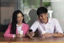 Attrayant jeune asiatique couple boire du café et en utilisant smartphone — Photo de stock