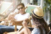 Amigos conversando no terraço de um clube de praia em Cingapura — Fotografia de Stock
