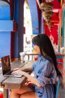 Attractive asian woman using laptop device at cafe — Stock Photo