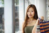 Jeune femme asiatique au centre commercial tenant sac — Photo de stock