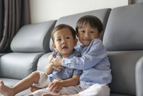 Two young siblings bonding on the sofa in the living room — Stock Photo
