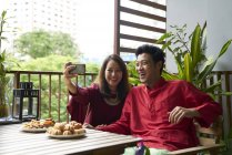 Young asian couple celebrating Hari Raya in Singapore together at home — Stock Photo