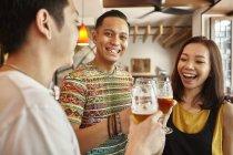 Giovani amici asiatici con birra insieme nel bar — Foto stock