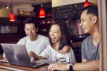 Jóvenes amigos asiáticos usando laptop junto en la barra - foto de stock