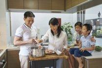Heureux asiatique famille préparation de la nourriture ensemble à la maison — Photo de stock