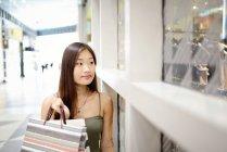 Mujer asiática joven en centro comercial de pie junto a la parte delantera de la tienda - foto de stock