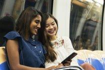 Jeunes filles asiatiques occasionnelles partage smartphone en train — Photo de stock