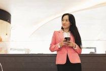 Jovem atraente asiático mulher usando smartphone no shopping — Fotografia de Stock