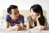 Mature asian casual couple lying in bed and looking at each other — Stock Photo