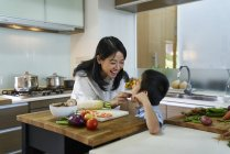 Happy young asian mother feeding son at kitchen — Stock Photo