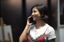 Молодая азиатская деловая женщина разговаривает на смартфоне в современном офисе — стоковое фото