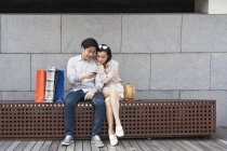 Young asian couple using smartphone together on bench — Stock Photo
