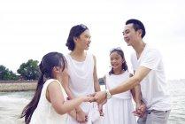 Felice famiglia asiatica trascorrere del tempo insieme sulla spiaggia — Foto stock