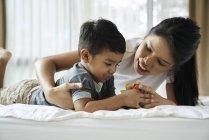 Madre vinculándose con su hijo en la cama - foto de stock