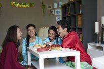 Jeune famille asiatique célébrant Hari Raya à Singapour et jouant jeu traditionnel — Photo de stock