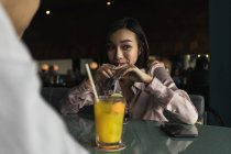 Young asian couple spending time together in bar with drinks — Stock Photo