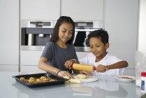 Молоді азіатські братів і сестер святкування Харі Райян разом вдома і приготування традиційних страв — стокове фото