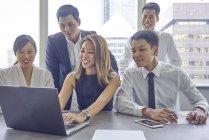 Молодые азиатские деловых людей, работающих с ноутбуком в современном офисе — стоковое фото